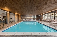 Indoor pool area with patio chairs and a wood-paneled ceiling