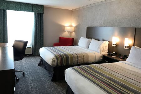 Hotel room with two queen beds, a work desk and a red arm chair