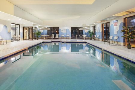 Brightly lit indoor pool with adjacent hot tub