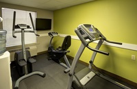Fitness room with a treadmill and a green accent wall
