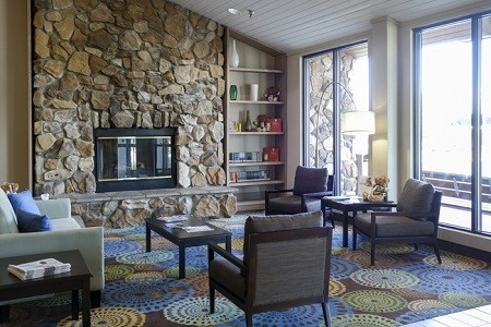 Sitting area in the hotel lobby with a fireplace, beautiful stonework and natural lighting