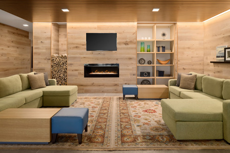Inviting hotel lobby with a fireplace and large green couches