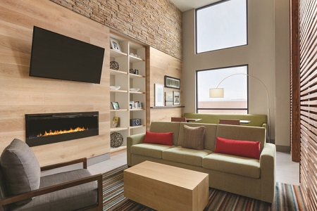 Lobby area with a light green sofa, gray armchair, fireplace and flat-screen TV