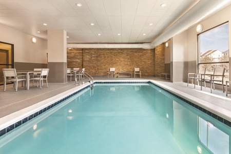 Indoor pool area with a large window, an exposed brick wall and white patio furniture
