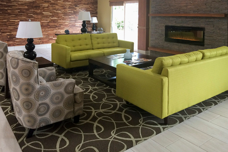 Lobby seating area with couches and armchairs next to a fireplace