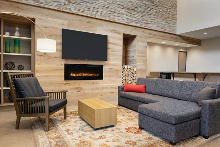 Hotel lobby with a fireplace, an armchair, a sectional and a flat-screen TV