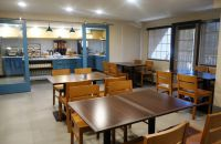 Breakfast area with tables, chairs and a servery with blue cabinets