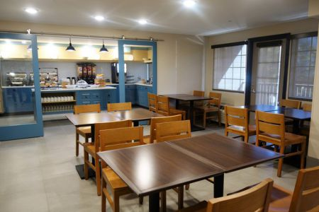 Breakfast servery and dining room with tables and chairs