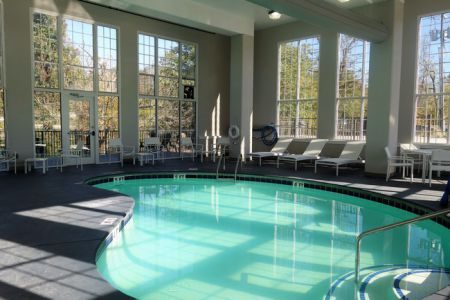 Indoor pool surrounded by lounge chairs and floor-to-ceiling windows