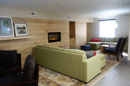 Welcoming hotel lobby with a fireplace, armchair and two green sofas