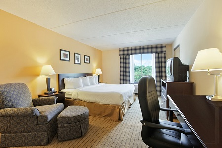 Hotel room with king bed, work desk and a chair with an ottoman