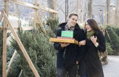 Couple carrying gifts at a Christmas tree farm