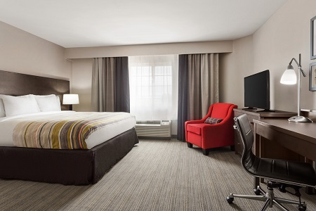 Hotel Room With A King Bed, A Red Armchair And A Flat Screen TV