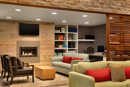 Hotel lobby with comfortable couches, a flat-screen TV and a fireplace