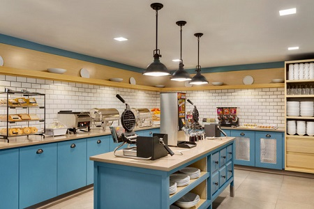Hotel breakfast room with waffle irons, a waffle mix dispenser, pastries and sky blue cabinets