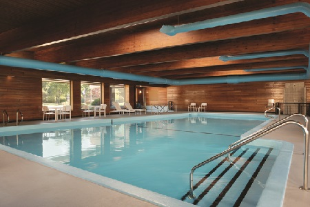Indoor pool and hot tub with wooden beams overhead