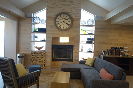 Hotel lobby with a gray sectional, a fireplace and a coffee station