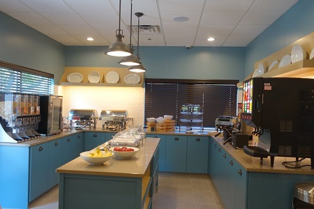 Breakfast area with cereal, fresh fruit, hot entrées and blue cabinets
