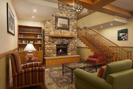 Hotel lobby with stone fireplace, wooden beams and staircase
