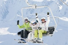 Three skiers riding a ski lift
