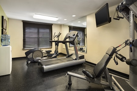 Fitness center with floor-to-ceiling mirrors and neutral walls
