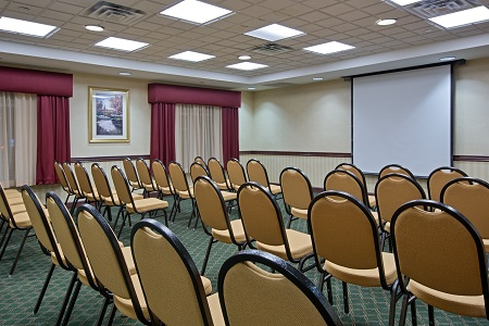 Meeting room with rows of chairs facing projector screen