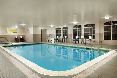 Spacious indoor pool area with seating and arched windows