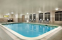 Indoor pool area with patio chairs and arched windows