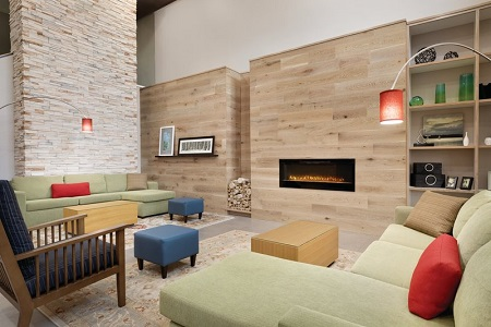 Inviting hotel lobby with green sectionals and a fireplace