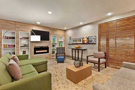 Welcoming lobby with a gray sofa, a green sectional and a flat-screen TV mounted above a fireplace