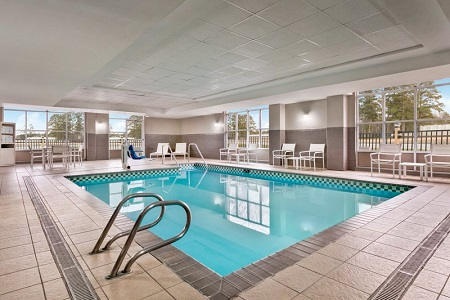 Indoor pool lined by patio chairs and large windows