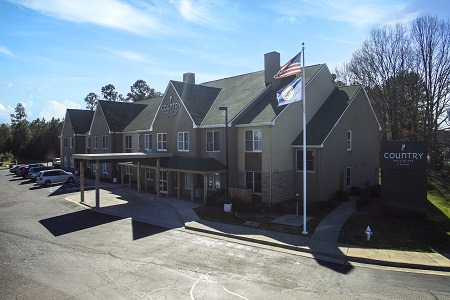 Exterior of the Country Inn & Suites with a large parking lot and carport