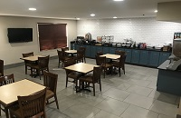 Breakfast area at hotel in Richmond with tables, chairs and a breakfast spread