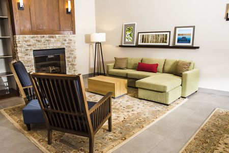 Welcoming lobby with a fireplace and green sofa
