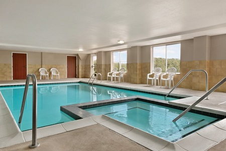 Indoor pool surrounded by white patio chairs