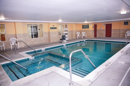 Indoor pool at hot tub area with white chairs and a rack of towels