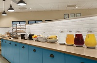 Breakfast servery with blue cabinets, pastries, fresh fruit and several juice options