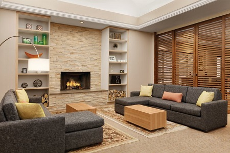 Welcoming hotel lobby with two gray sectionals in front of a stone fireplace