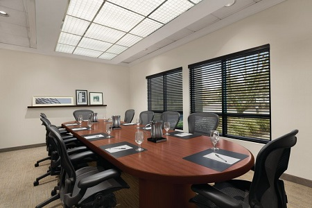 Boardroom table surrounded by ergonomic chairs and set with pens, stationery and glasses