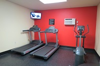Fitness center with two treadmills and elliptical against red wall