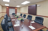Boardroom setup with pens, stationery and black leather chairs