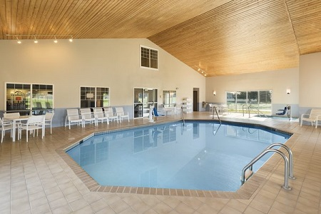 Sparkling indoor pool surrounded by white patio furniture