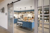 Breakfast area with pastries and cereal dispensers on blue cabinetry