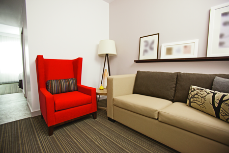 Hotel suite living area with a sofa and a red armchair