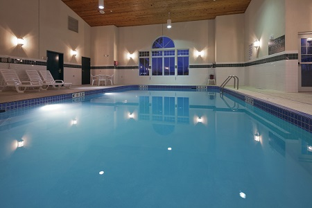 Indoor pool with white lounge chairs to the left