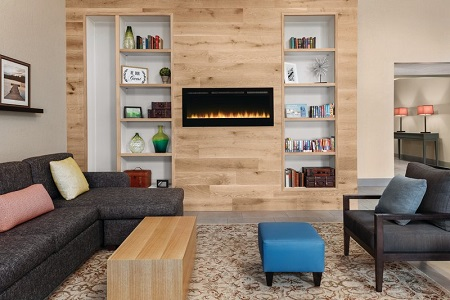 Welcoming hotel lobby with a modern fireplace, gray armchair and gray sectional