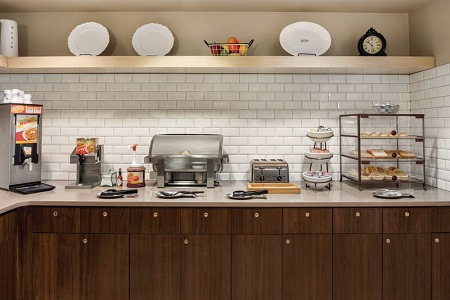 Breakfast servery with wooden cabinets, hot meal options and a make-your-own waffle station