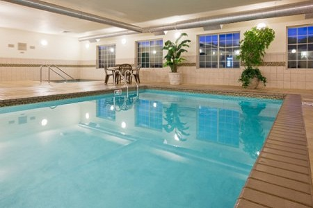 Sparkling indoor pool with accent plants and patio furniture