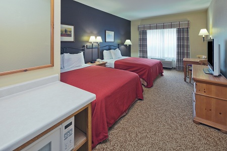 Two Queen Beds With Red Accenticrowave In Hotel Room