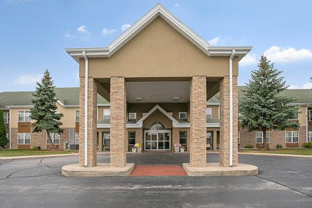 Exterior of the Country Inn & Suites with a large carport